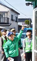 設置された防犯カメラを見上げる地元の住民ら=島根県出雲市で、山田英之撮影