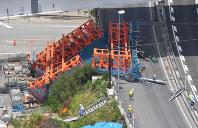新名神高速道路の工事現場で倒れた仮受け台=大阪府箕面市で2016年5月19日午前11時53分、本社ヘリから西本勝撮影