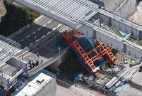 新名神高速道路の工事現場で倒れた仮受け台=大阪府箕面市で2016年5月19日午前11時56分、本社ヘリから西本勝撮影