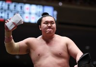 豪栄道を降して全勝を守り懸賞を受け取る白鵬=東京・両国国技館で2016年5月19日、猪飼健史撮影