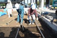 被爆前の街並みの遺構の発掘調査で、地層を掘り返す作業員ら=広島市中区で2015年11月