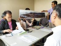 福島第1原発事故で強制避難となった地域の写真を見せて「明日は我が身と考えて」と訴える市民団体のメンバー=福井県高浜町で、高橋一隆撮影