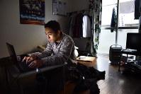 介護福祉士の試験に向けて勉強をする佐藤祐輔さん。電気代を節約するため、日中は部屋の電気も暖房もできるだけつけないという=東京都府中市で、竹内紀臣撮影