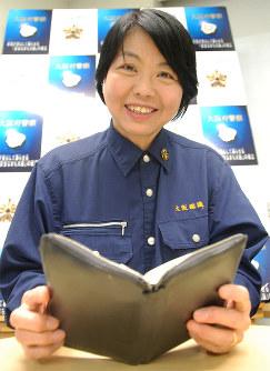 大事にしている手帳を見る久原昭子警部=大阪府警本部で、山田毅撮影