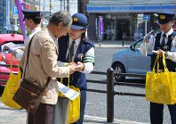 交通死亡事故の抑止を通行人に訴える稲沢署員=稲沢市で