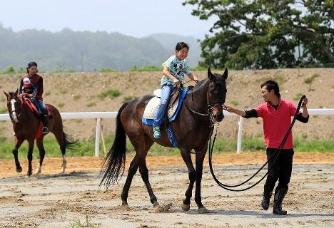 整備された共同錬馬場で乗馬体験をする子どもたち=福島県南相馬市で2016年5月22日、梅村直承撮影