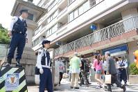 平日でも混雑する神宮前交差点付近で、通行人に警戒を呼びかける警察官ら=渋谷区で