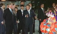 【2000年主要国首脳会議】森首相主催の夕食会を終え沖縄県の民族衣装を着た女性に見送られ首里城を後にする森首相(中央)とクリントン米大統領ら各国首相