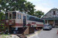 山岡駅かんてんかん(右奥)の店舗裏側に保存されている「アケチ1号」=恵那市山岡町で