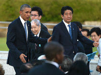 U.S. President Barack Obama and Japanese Prime Minister Shinzo Abe leave Hiroshima Peace Memorial Park after speaking with A-bomb survivors, on May 27, 2016. (Mainichi)
