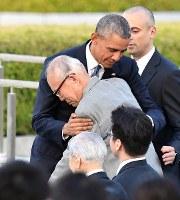 所感を述べた後、米捕虜被爆者の調査をする森重昭さんを抱きしめるオバマ米大統領。中央手前は坪井直・日本被団協代表委員=広島市中区の平和記念公園で2016年5月27日午後6時8分、久保玲撮影