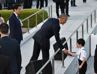 原爆ドーム付近に向かう途中、参列した子どもと握手を交わすオバマ米大統領(中央)。左は安倍首相=広島市中区の平和記念公園で2016年5月27日午後6時9分(代表撮影)