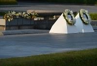 オバマ米大統領が原爆慰霊碑に献花した花(右)と安倍晋三首相が献花した花=広島市中区の平和記念公園で2016年5月27日午後6時、久保玲撮影