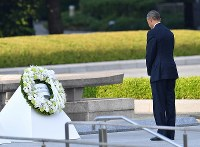U.S. President Barack Obama stands with his head slightly bowed after laying a wreath of flowers in front of the cenotaph for the A-bomb victims at Hiroshima Peace Memorial Park on May 27, 2016. (Mainichi)