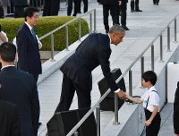 On his way to the Hiroshima Peace Memorial -- more commonly known as the Genbaku Dome or the Atomic Bomb Dome -- U.S. President Barack Obama (center) shakes hands with a child who attended the event at Hiroshima Peace Memorial Park on May 27, 2016. (Pool photo)