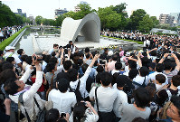 A crowd descends upon the cenotaph for the A-bomb victims at Hiroshima Peace Memorial Park to get a glimpse of the wreath placed there by U.S. President Barack Obama, in Hiroshima's Naka Ward on May 27, 2016. (Mainichi)