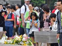 オバマ米大統領来訪から一夜明けた平和記念公園で、原爆慰霊碑に向かって手を合わせる人たち=広島市中区で2016年5月28日午前10時48分、小関勉撮影