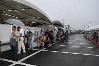 雨の中、並んで整理券の発行を待つ人々=熊本県益城町のグランメッセ熊本で5月28日午前7時7分頃、福岡賢正撮影