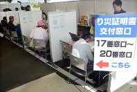 罹災証明書を交付される被災者=熊本県益城町福富のグランメッセ熊本で2016年5月20日午前9時4分、宮崎稔樹撮影