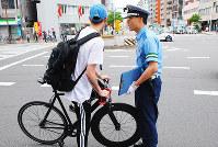 警察官の注意を聞く自転車運転者=大阪市浪速区で、千脇康平撮影