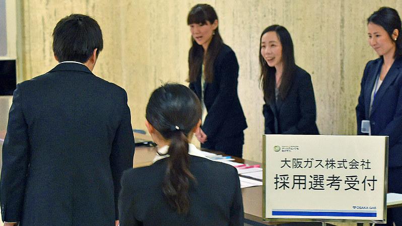 大阪ガスのグループディスカッションに参加するため受付に向かう学生たち(手前)=大阪市中央区で6月1日、川平愛撮影