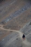 左翼ゲリラの拠点だったアヤクチョ県からの移住者が大勢住むリマ市南部ビジャエルサルバドル地区。パンをつめた袋を両手に提げた女性が、舗装されていない山道を下りていく=2016年5月28日午後5時29分、朴鐘珠撮影