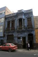 アルベルト・フジモリ政権下の軍特殊部隊による市民虐殺「バリオスアルトス事件」が起きた民家(中央の青い壁)。特殊部隊は道路に面した玄関から突入した=リマ市内で2016年5月26日午後2時11分、朴鐘珠撮影