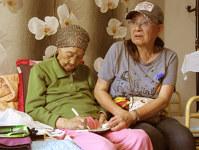 ヘルパーが帰った後、夜は1人きりになる。臼杵敬子さん(右)の訪問を喜んだ元慰安婦(左)は日韓合意の成果を見ぬまま今年2月に亡くなった=ソウルで2015年5月21日