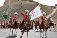 「第5回アジアインドア・マーシャルアーツゲームズ」のカウントダウンイベントで出発するアハルテケ種の馬。後ろがニサ遺跡(旧ニサ)=トルクメニスタンで5月5日、山本太一撮影
