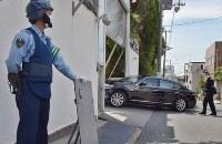 警察官が警戒する中、山口組総本部に入る車両=神戸市灘区で2016年6月6日午前9時55分
