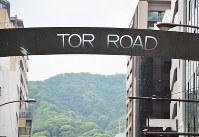 「TOR ROAD(トア・ロード)」と書かれたゲートの向こうには六甲山地がのぞく=神戸市中央区で、石川貴教撮影