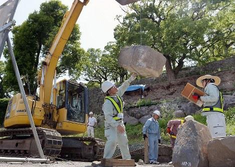 熊本地震で熊本城の石垣から崩落し、番号を書かれて運び出される石(中央)=熊本市中央区で2016年6月7日午後2時21分、津村豊和撮影