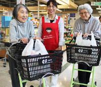 「楽々カート」で買い物を済ませ笑顔の女性たち。エプロンをつけた女性は「お買い物おたすけ隊」のボランティア=神戸市西区で、木田智佳子撮影