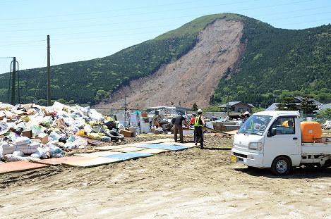 がれきの仕分けに励む学生ら。奥には崩落した阿蘇大橋一帯で起きた土砂崩れの跡が残る=熊本県南阿蘇村河陽で、竹内望撮影