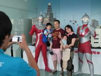 東京スカイツリーの展望台「天望回廊」に現れたウルトラマン(右)やウルトラセブン(左)と記念写真を撮る家族=墨田区押上1で