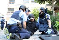犯人役を取り押さえる警察官たち=名古屋市中村区で10日