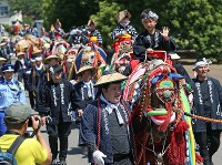 Children on horseback wave at a cheering crowd along the road in Takizawa, Iwate Prefecture, on June 11, 2016, during the annual