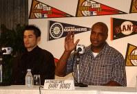 日米野球のため来日し、会見で紹介を受け手を挙げるバリー・ボンズ。左はイチロー=2002年11月06日、山下浩一撮影
