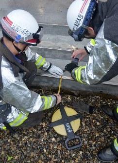 小学校体育館の出入り口付近で計12㍍の地割れとみられる亀裂を調べる消防=函館市臼尻小学校で
