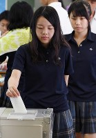 A student casts a ballot in a mock referendum on constitutional revisions at Tokyo Metropolitan Takashima High School in Itabashi Ward, Tokyo, on June 17, 2016. (Mainichi)