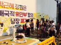 慰安婦を象徴する少女像を囲む支援者ら。背後には日韓合意廃棄を訴えるスローガンが掲げられている=ソウルの日本大使館前で17日、米村耕一撮影