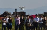 ドローンのデモ飛行を見る参加者たち=蒲郡市松原町の竹島ベイパークで