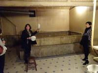 パナマホテル地下にある大衆浴場を案内するジョンソンさん(左)=米シアトルのパナマホテルで2016年5月、野沢和弘撮影