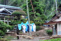 Rescue workers carry a resident who was pulled from a house hit by a landslide, in Kita Ward, Kumamoto, on June 21, 2016. (Mainichi)