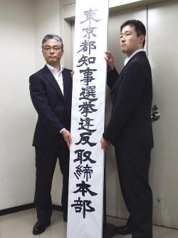 都知事選挙違反取締本部の看板を設置する警察官=千代田区霞が関の警視庁本部で