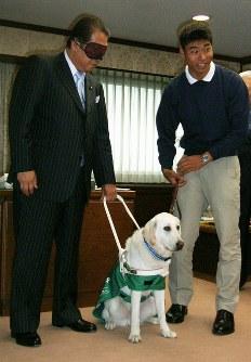 プログラム導入に先立ち、鳩山邦夫法相(左)もアイマスクを着け盲導犬を体験した=法務省で2008年6月9日、石川淳一撮影