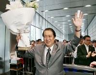 日本郵政社長人事をめぐり、西川善文社長の続投に反対していた鳩山邦夫総務相が辞任する異例の展開となった。麻生太郎首相の求心力は一段と低下、鳩山総務相は花束を手に総務省を後にした=東京・霞が関で2009年6月15日午後、尾籠章裕撮影