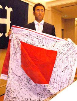 残留を求めるファンからのメッセージの書かれた旗を広げる黒田博樹投手=広島市中区のホテルで2006年11月6日撮影、井上梢撮影