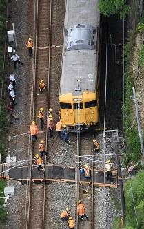 脱線した電車を調べる作業員ら=広島市安芸区で2016年6月23日午前9時7分、本社ヘリから西本勝撮影