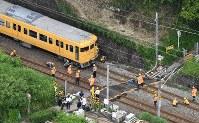脱線した電車を調べる作業員ら=広島市安芸区で2016年6月23日午前9時6分、本社ヘリから西本勝撮影